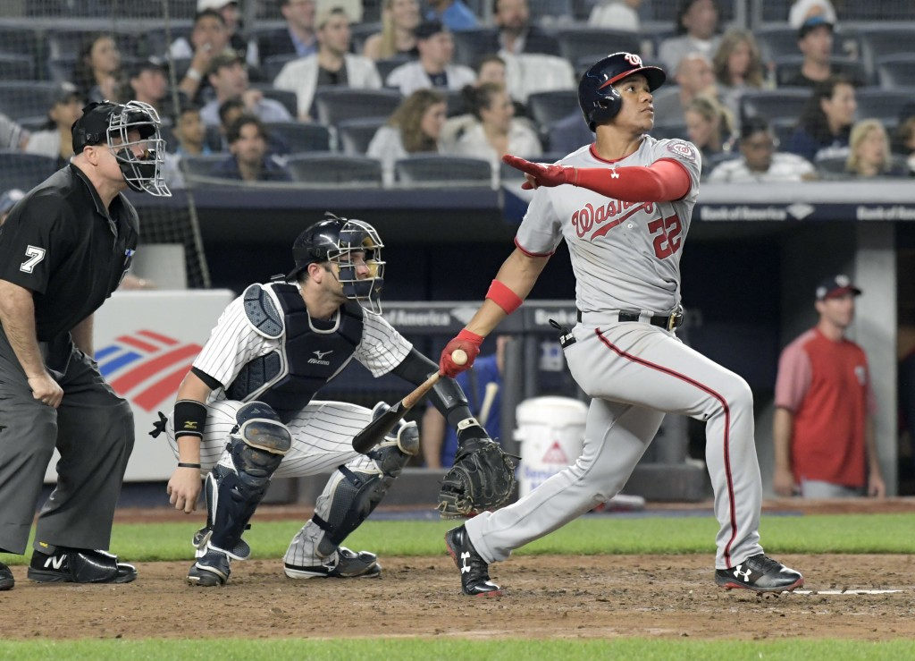 Washington Nationals' Juan Soto watches his home run in front New York Yankees catcher Austin Romine (28) and umpire Brian O'Nora uring the seventh in