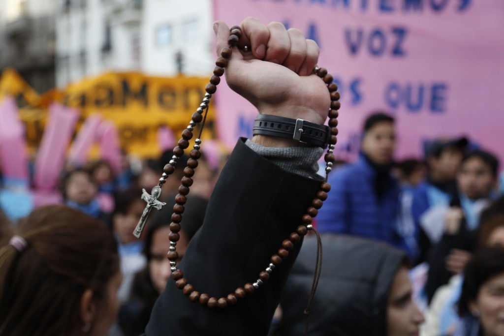 Pro-life protesters rally against a proposed law to legalize abortion, with one holding a Catholic rosary, near Congress in Buenos Aires, Wednesday, J
