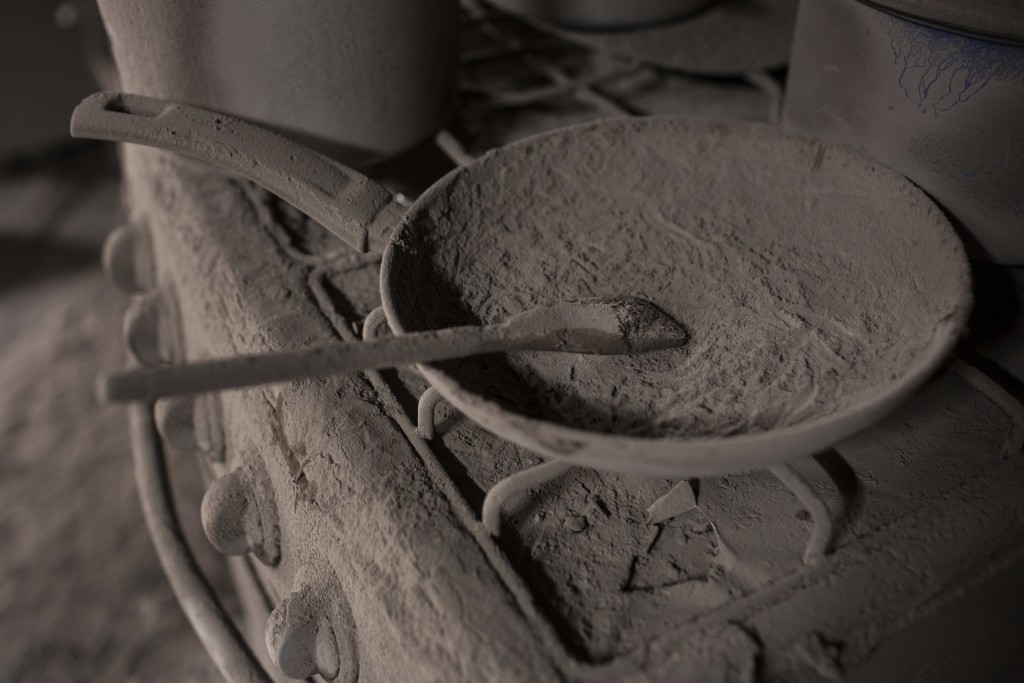 This June 11, 2018 photo shows an ash-coated pan and wooden spoon on a stovetop inside a home covered in volcanic ash spewed from the Volcan de Fuego