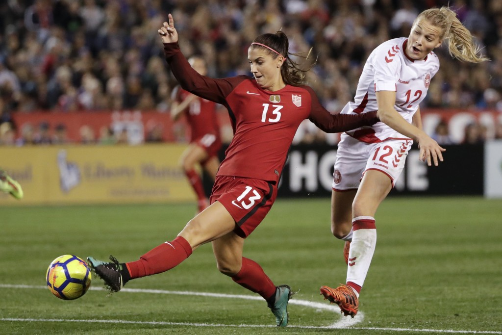 FILE - In this Jan. 21, 2018, file photo, United States forward Alex Morgan, left, shoots on goal as Denmark forward Stine Larsen, right, defends duri