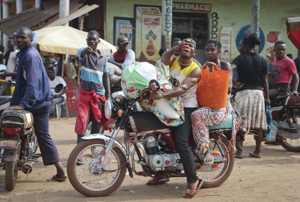 In this photo taken Saturday, June 2, 2018, a motorcycle taxi driver carries a passenger through the streets of Mbandaka, Congo. Hundreds are being va