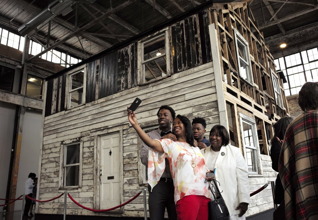 FILE - In this April 1, 2018 file photo, Cheryl Galloway, of Providence, R.I., uses a mobile phone to take a photo with family members in front of the