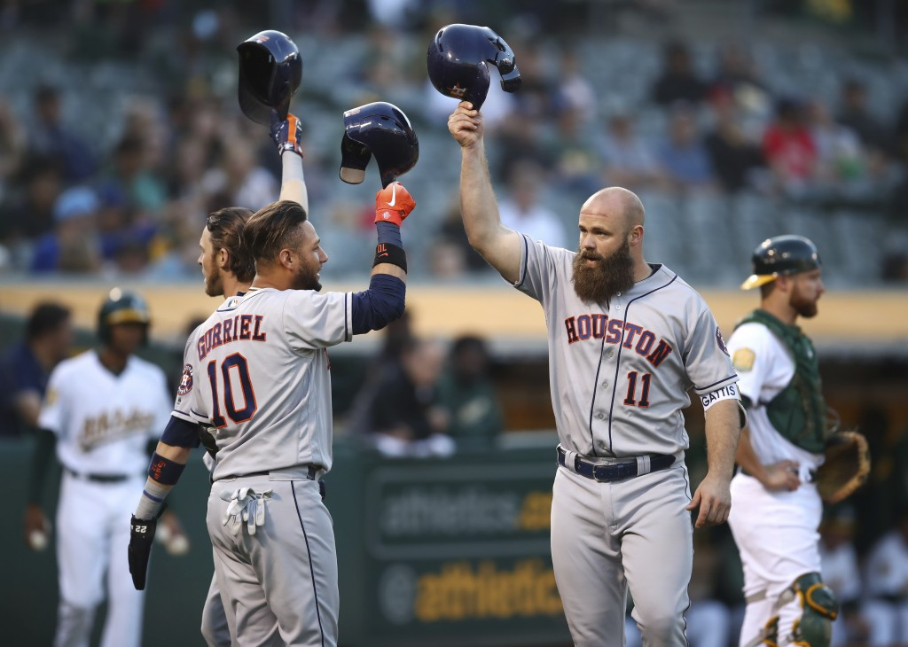 Houston Astros' Evan Gattis, right, celebrates with Yuli Gurriel (10) and Josh Reddick, left, after hitting a three-run home run off Oakland Athletics