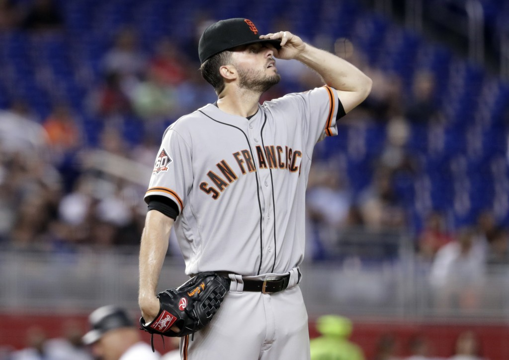 San Francisco Giants starting pitcher Andrew Suarez adjusts his cap during the fourth inning of the team's baseball game against the Miami Marlins, We