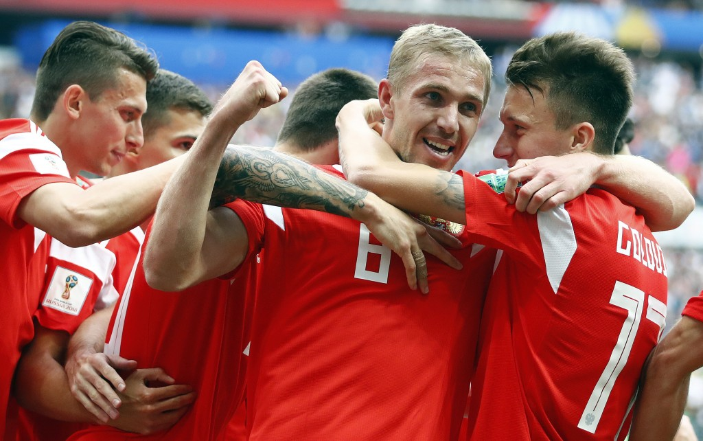 Russia's Yuri Gazinsky celebrates with teammates after scoring his side's first goal during the group A match between Russia and Saudi Arabia which op