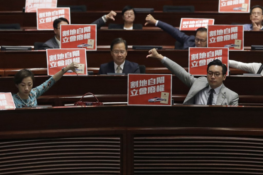 Pro-democracy lawmakers react after a controversial bill had passed at legislative chamber In Hong Kong, Thursday, June 14, 2018. The Hong Kong Legisl