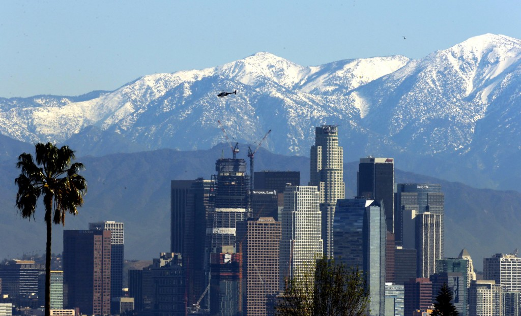 File - In this Jan. 12, 2016 file photo, the snow-capped San Gabriel Mountains stand as a backdrop to the downtown Los Angeles skyline. An initiative