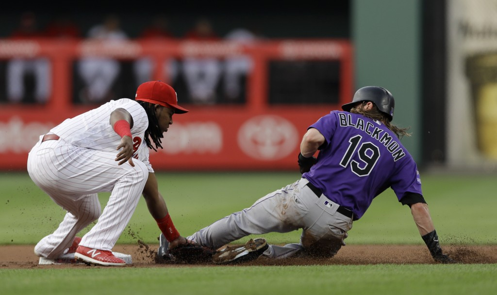 Philadelphia Phillies third baseman Maikel Franco, left, tags out Colorado Rockies' Charlie Blackmon at second base after Blackmon tried to steal duri...