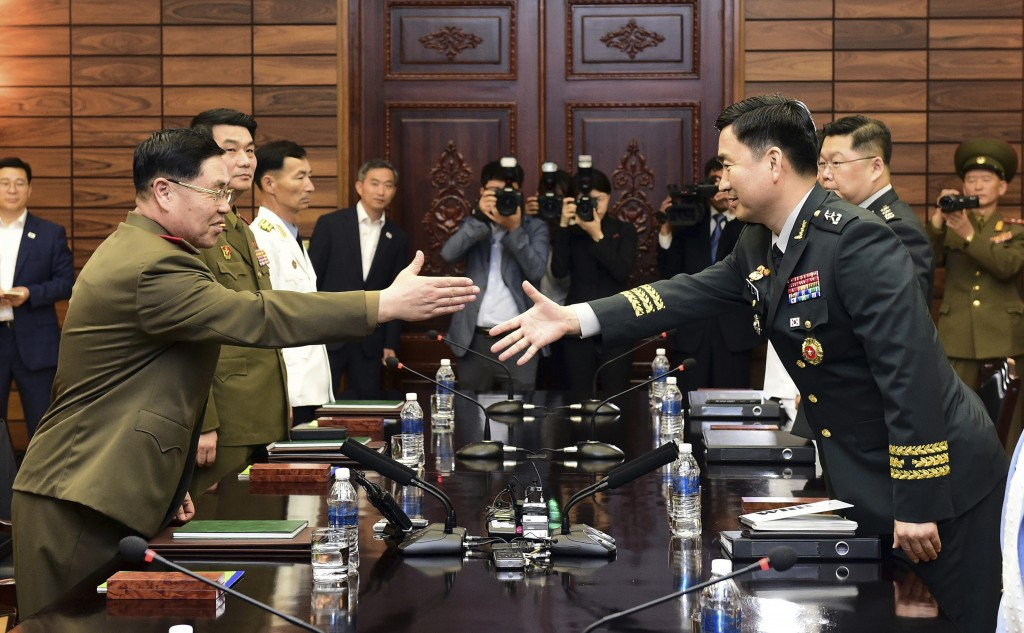 In this photo provided by South Korea Defense Ministry, South Korean Maj. Gen. Kim Do-gyun, right, tries to shakes hands with his North Korean counter
