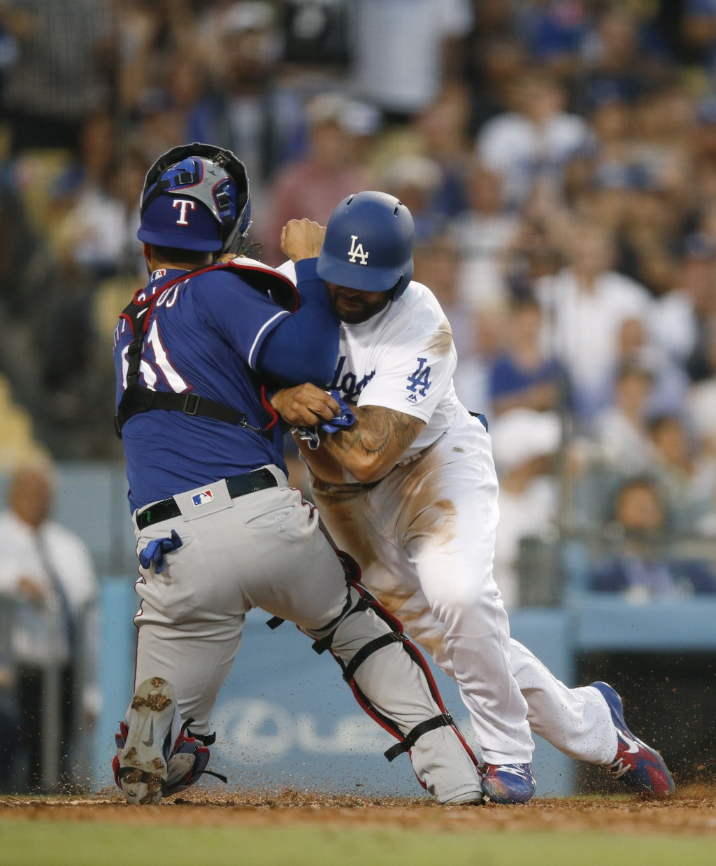 Los Angeles Dodgers' Matt Kemp, right, shoves Texas Rangers catcher Robinson Chirinos while trying to score on a single hit by Enrique Hernandez durin
