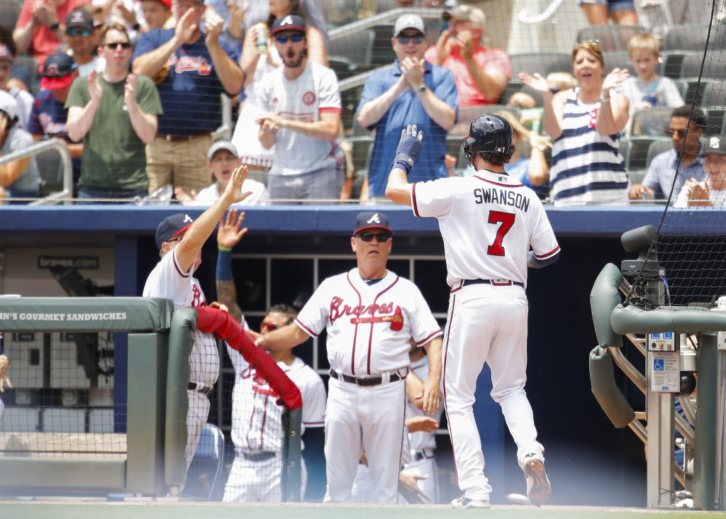 Atlanta Braves' Dansby Swanson (7) celebrates scoring off a single by Freddie Freeman in the fourth inning of a baseball game against the New York Met