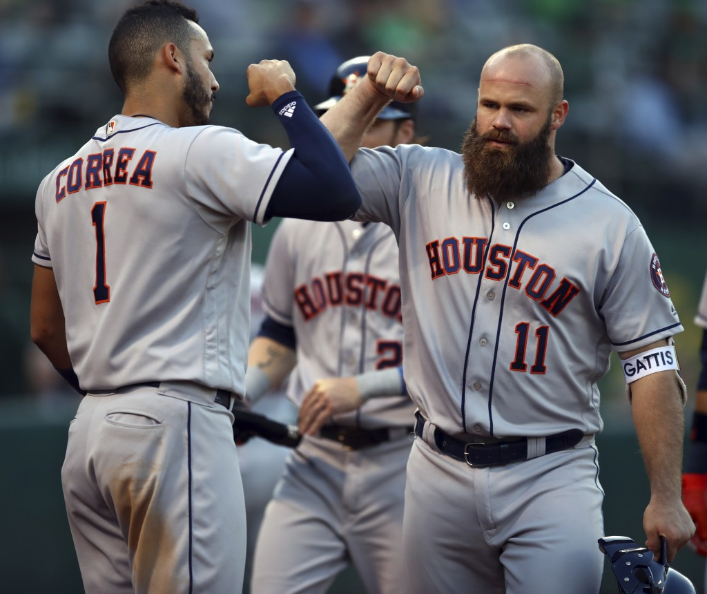 Houston Astros' Evan Gattis, right, celebrates with Carlos Correa (1) after hitting a three-run home run off Oakland Athletics' Emilio Pagan during th