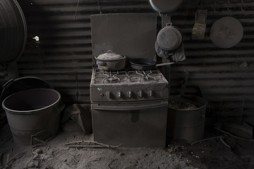This June 11, 2018 photo shows a kitchen blanketed in volcanic ash spewed by the Volcan de Fuego or Volcano of Fire, in San Miguel Los Lotes, Guatemal