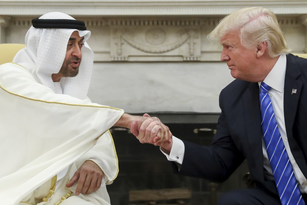 FILE - In this May 15, 2017, file photo, U.S. President Donald Trump, right, shakes hands with Abu Dhabi's crown prince, Sheikh Mohammed bin Zayed Al