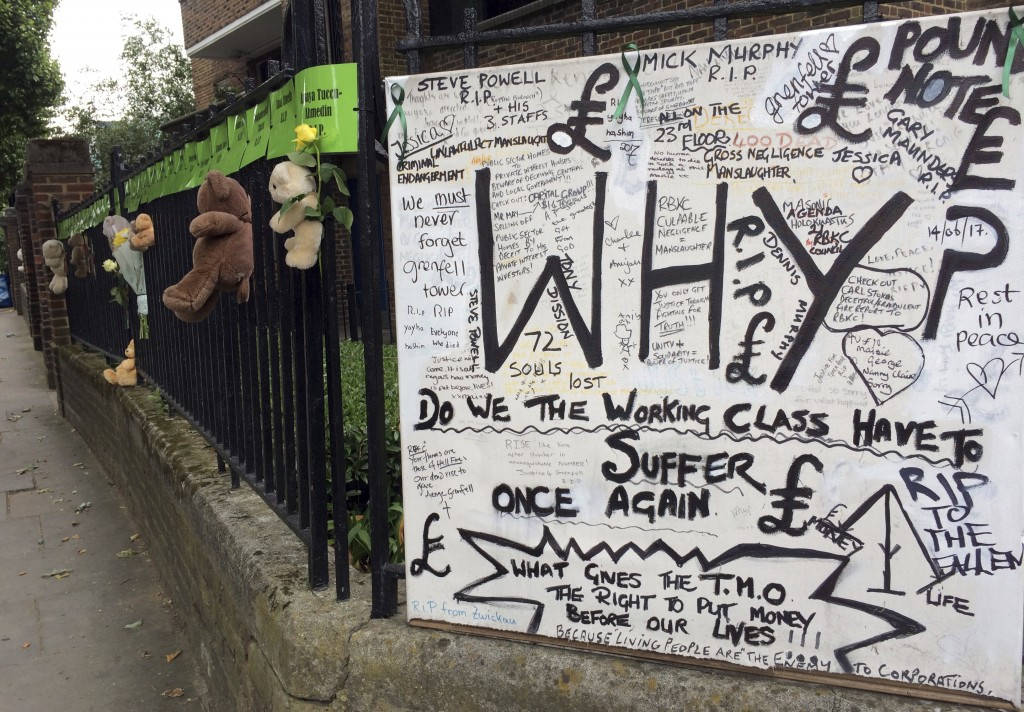 Tributes are tied to a fence, Thursday, June 14, 2018, in support of those affected by the massive fire in Grenfell Tower in London. A year ago, Londo