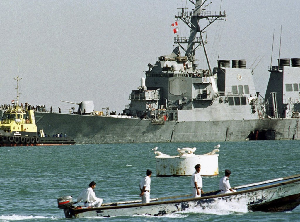 FILE - In this Oct. 29, 2000, file photo, a Yemeni police boat passes by the stricken USS Cole as it is pulled out of Aden port by Yemeni tugboats to
