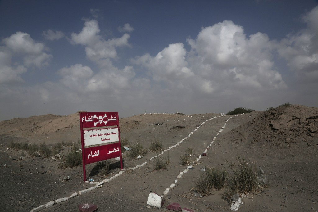 "This Feb. 15, 2018, photo shows a sign with Arabic that reads, ""danger mines, danger mines"" on the highway from Abyan to Aden in Yemen. (AP Photo/Nari"