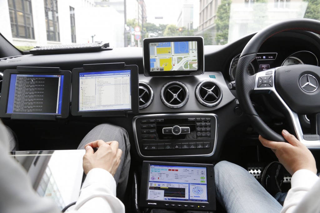 In this May 31, 2018, photo, a car monitor shows a 3D digital map as it's driven through Tokyo streets. Technology companies are racing to develop ult