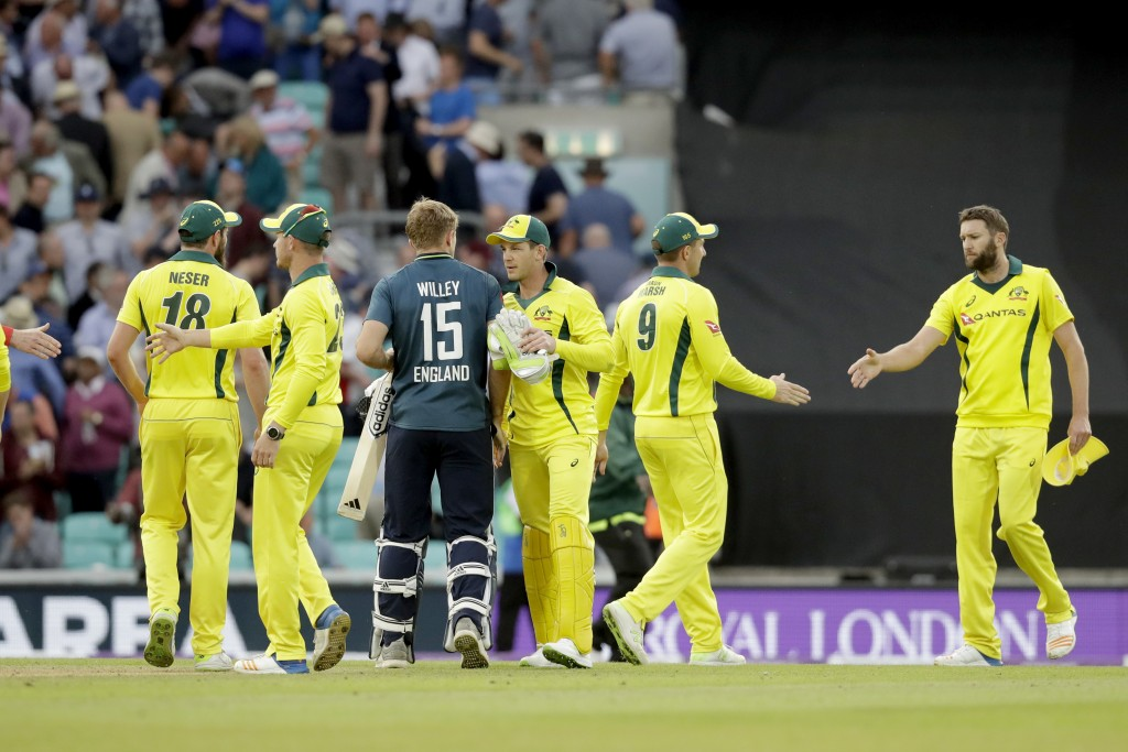 England's David Willey shakes hands with Australia captain Tim Paine, third right, after hitting a six to win the match during the one-day cricket mat