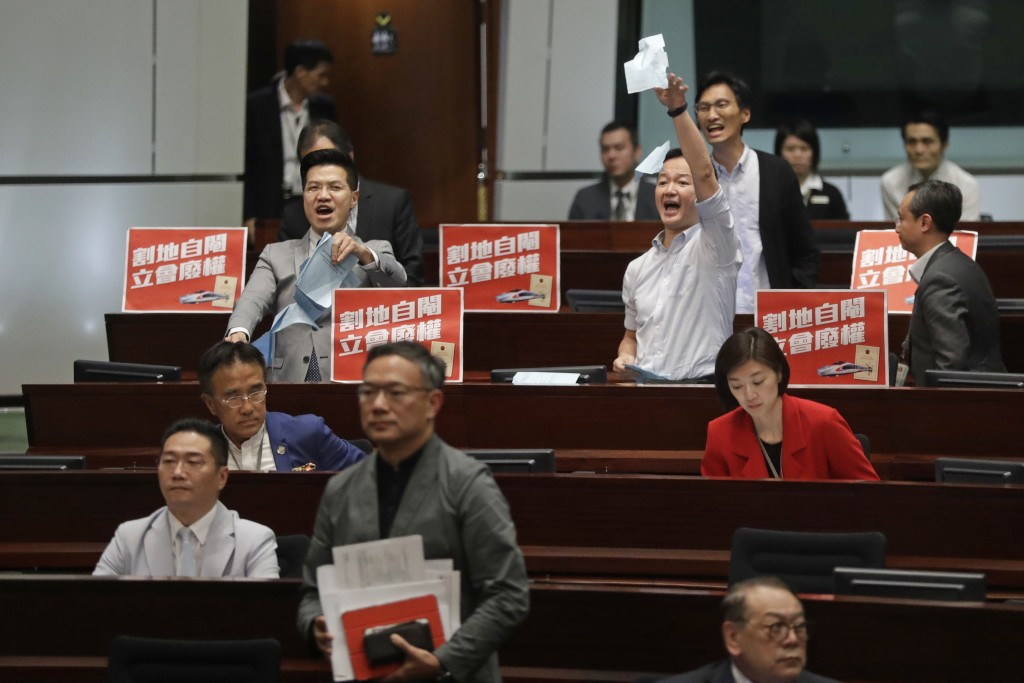 Two pro-democracy lawmakers, at the back, shout and tear up the government documents after a controversial bill had passed at legislative chamber In H