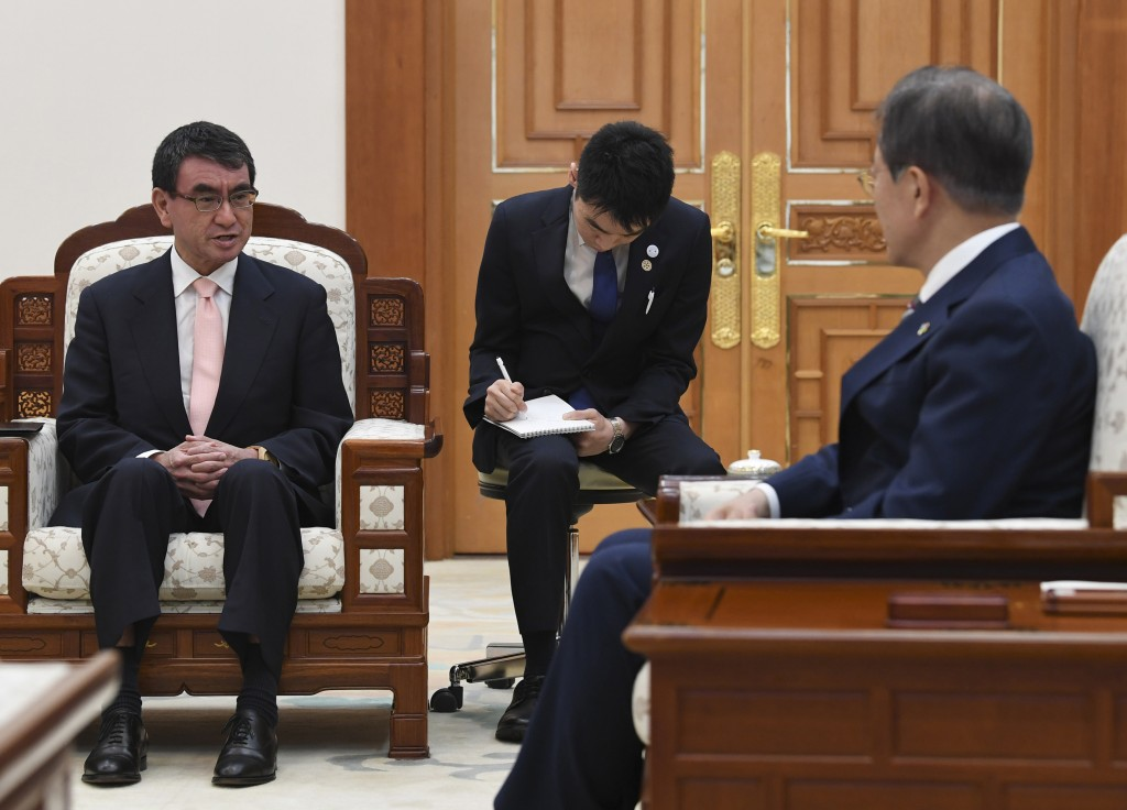 South Korean President Moon Jae-in, right, talks with Japanese Foreign Minister Taro Kono during their meeting at the presidential Blue House, Thursda