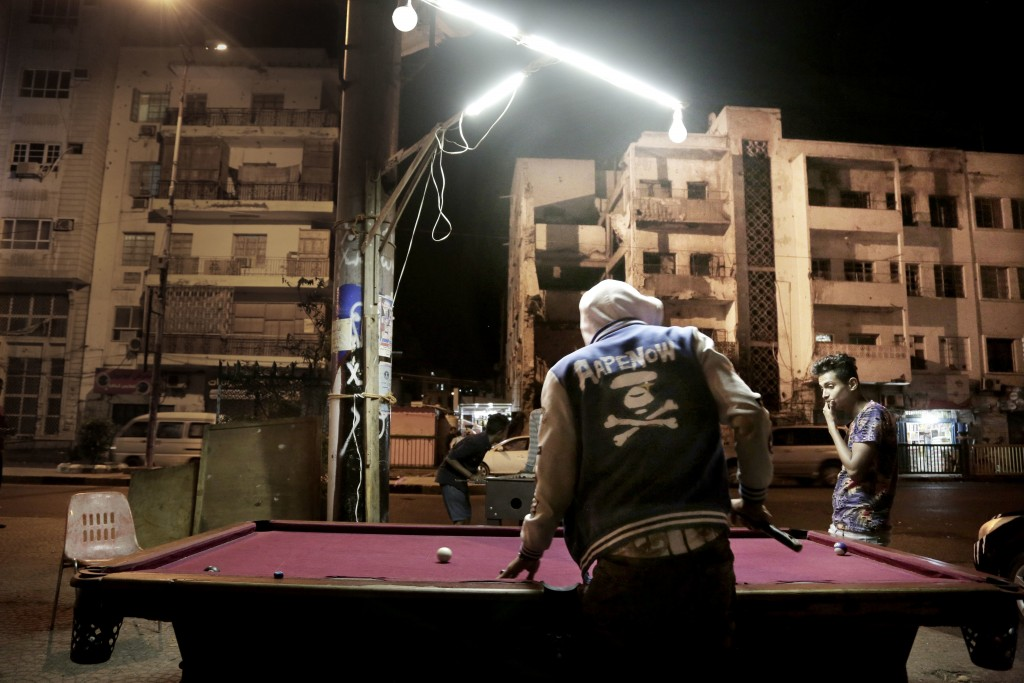 In this Feb. 15, 2018, photo, youth play pool on a street in front of damaged buildings due to the war in Aden, Yemen. Many damaged buildings are holl