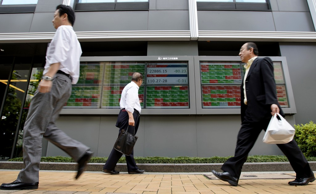 People walk past an electronic stock board of a securities firm in Tokyo, Thursday, June 14, 2018. Asian stock markets slumped on Thursday with South