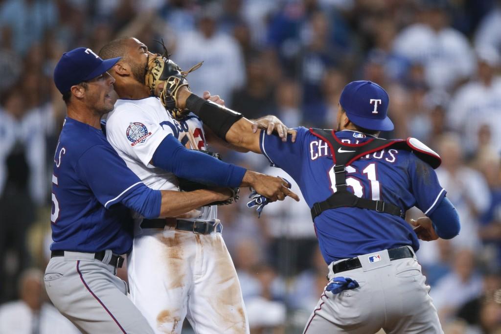 Texas Rangers starting pitcher Cole Hamels, left, restrains Los Angeles Dodgers' Matt Kemp as Kemp scuffles with Rangers catcher Robinson Chirinos dur