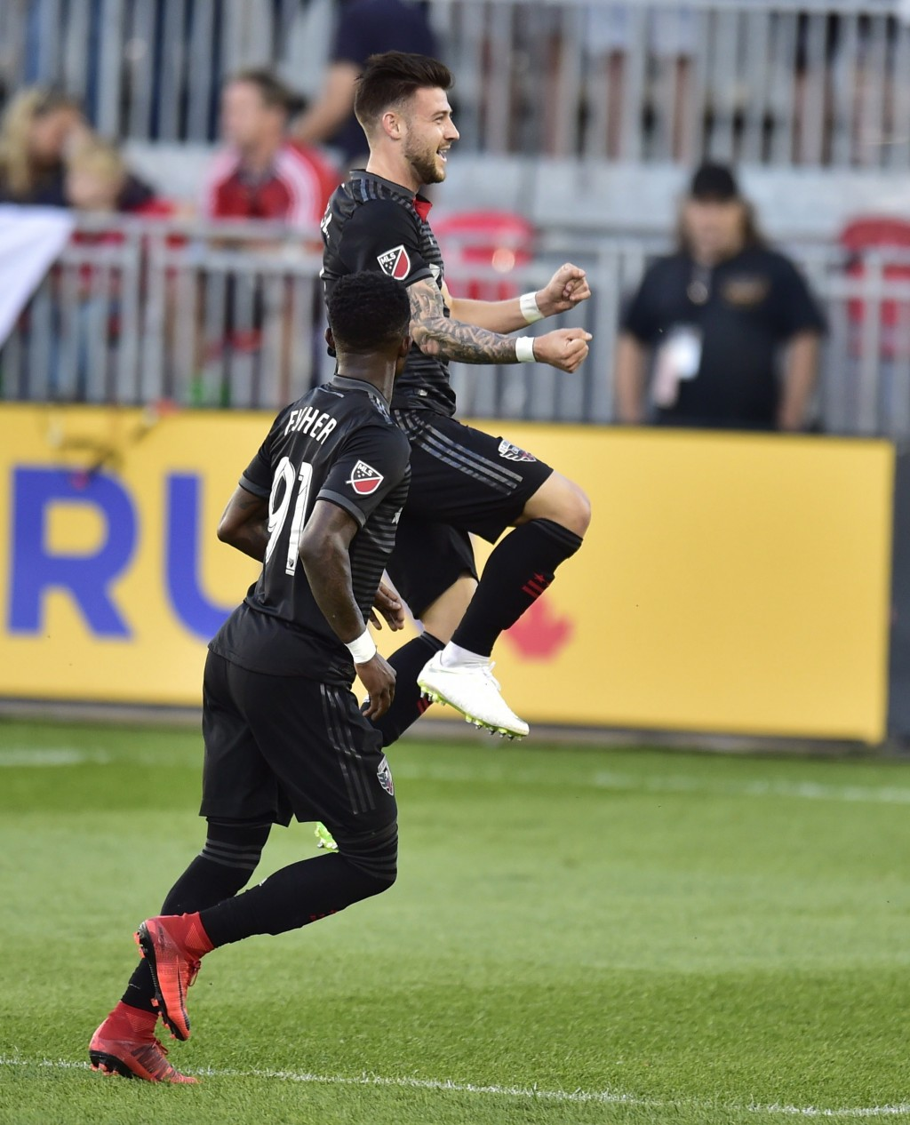D.C. United forward Paul Arriola celebrates his goal against Toronto FC with teammate Oniel Fisher (91) during the first half of an MLS soccer match W