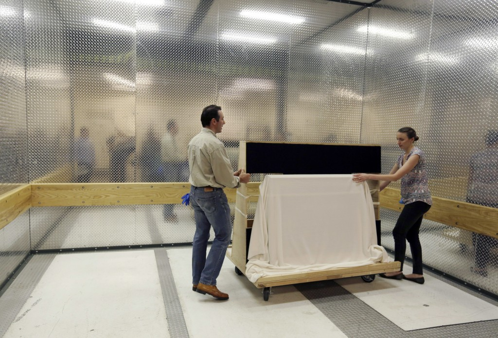 Collections manager/registrar Michelle Moskal, right, and curator Mark Turdo move the covered Commander-in-Chief's Standard in a freight elevator to a