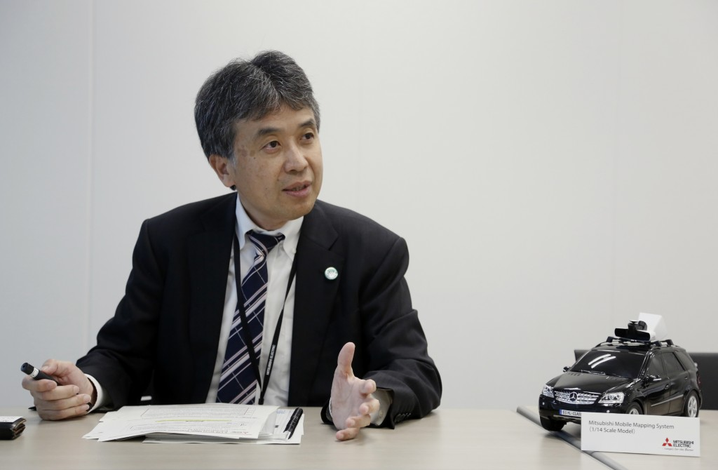 In this May 31, 2018, photo, Mitsubishi Electric Corp. Senior General Manager Yasuhide Shibata, who oversees the mapping project, speaks on some of th