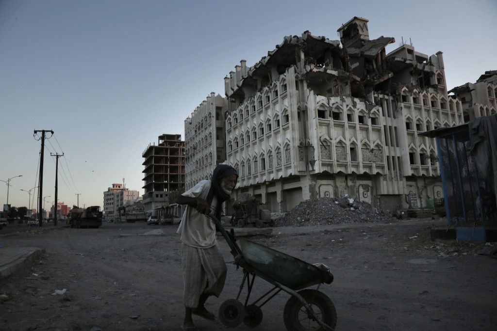 In this Feb. 13, 2018, photo, a elderly man walks past a damaged building from the 2015 war in Aden, Yemen. Violence, famine and disease have ravished