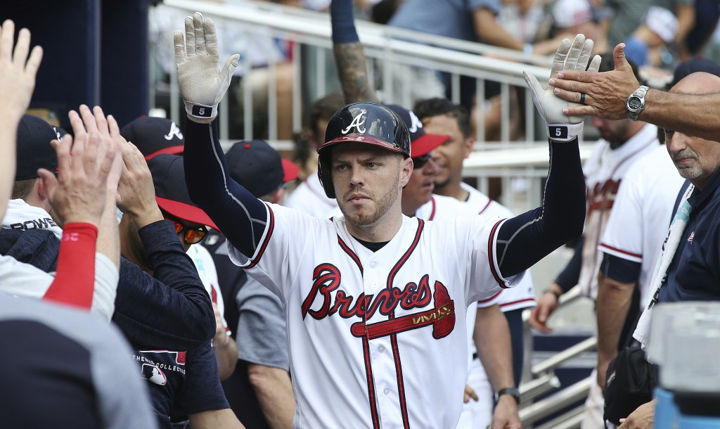 Atlanta Braves Freddie Freeman gets high-fives in the dugout after hitting a solo home run in the eighth inning of a baseball game against the New Yor...