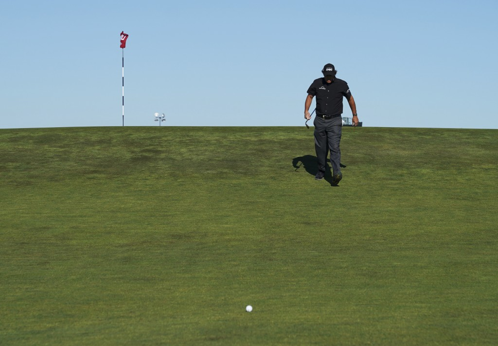 Phil Mickelson walks back down to his ball after checking his line to the pin on the tenth green during the first round of the U.S. Open Golf Champion