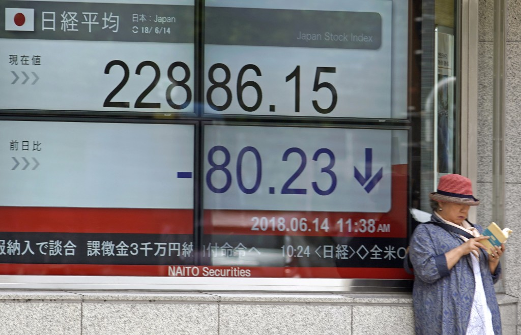 A woman reads a book in front of an electronic stock board showing Nikkei's stock index in Tokyo, Thursday, June 14, 2018. Asian stock markets slumped