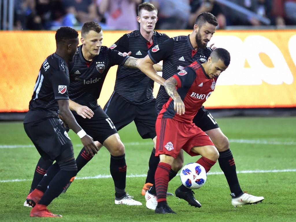 Toronto FC forward Sebastian Giovinco controls the ball as D.C. United's Oniel Fisher, Frederic Brillant, Chris Durkin and Steve Birnbaum, from left,