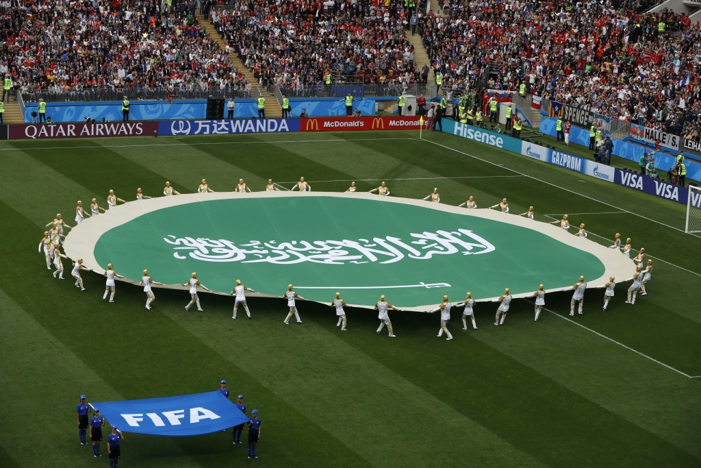 Volunteers hold the flag of Saudi Arabia ahead of the group A match between Russia and Saudi Arabia which opens the 2018 soccer World Cup at the Luzhn