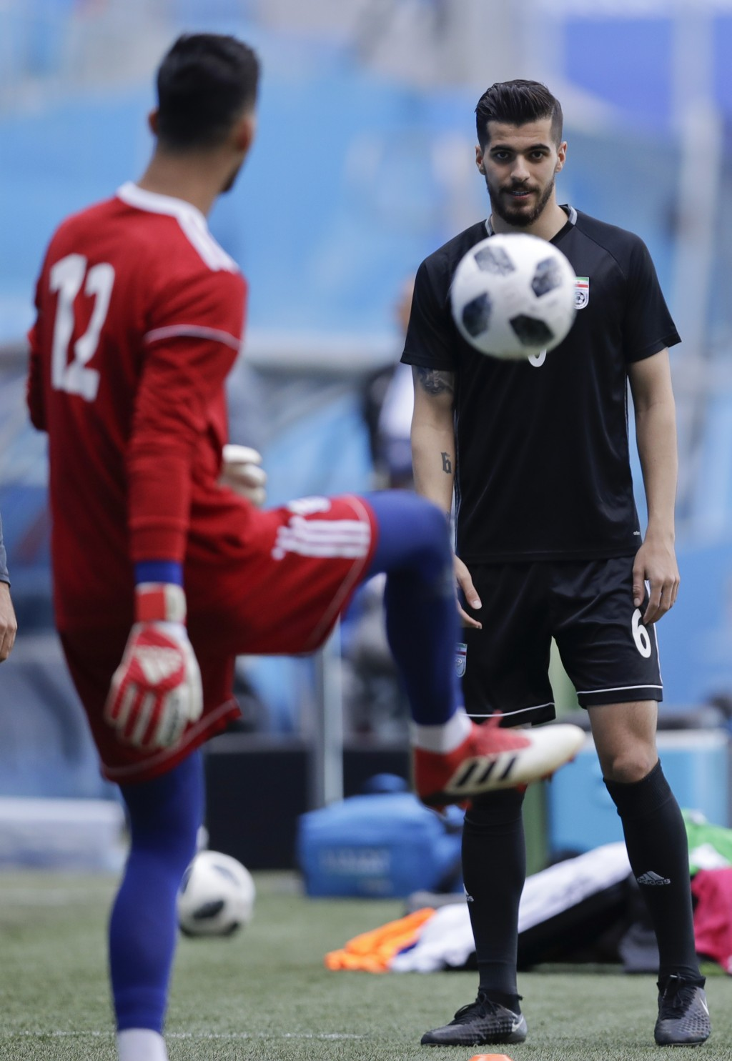 Iran goalkeeper Amir Abedzadeh, left, and Iran's Saeid Ezatolahi practice during the official training of Iran on the eve of the group B match between