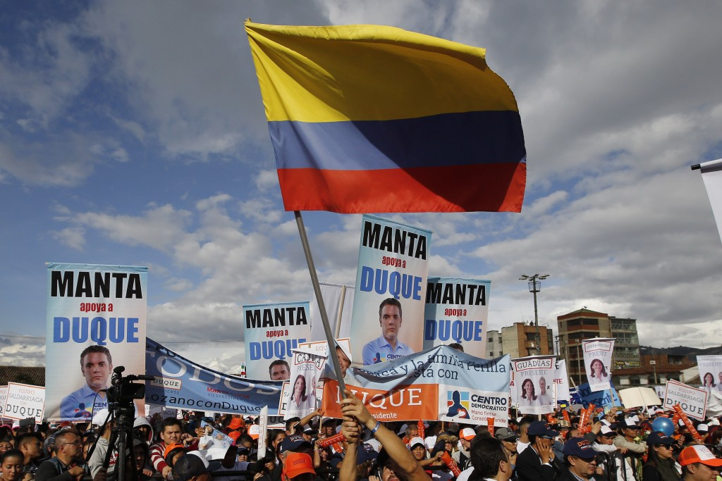 FILE - In this May 12, 2018 file photo, a supporters of Ivan Duque, presidential candidate for Democratic Center party, waves a Colombian flag during