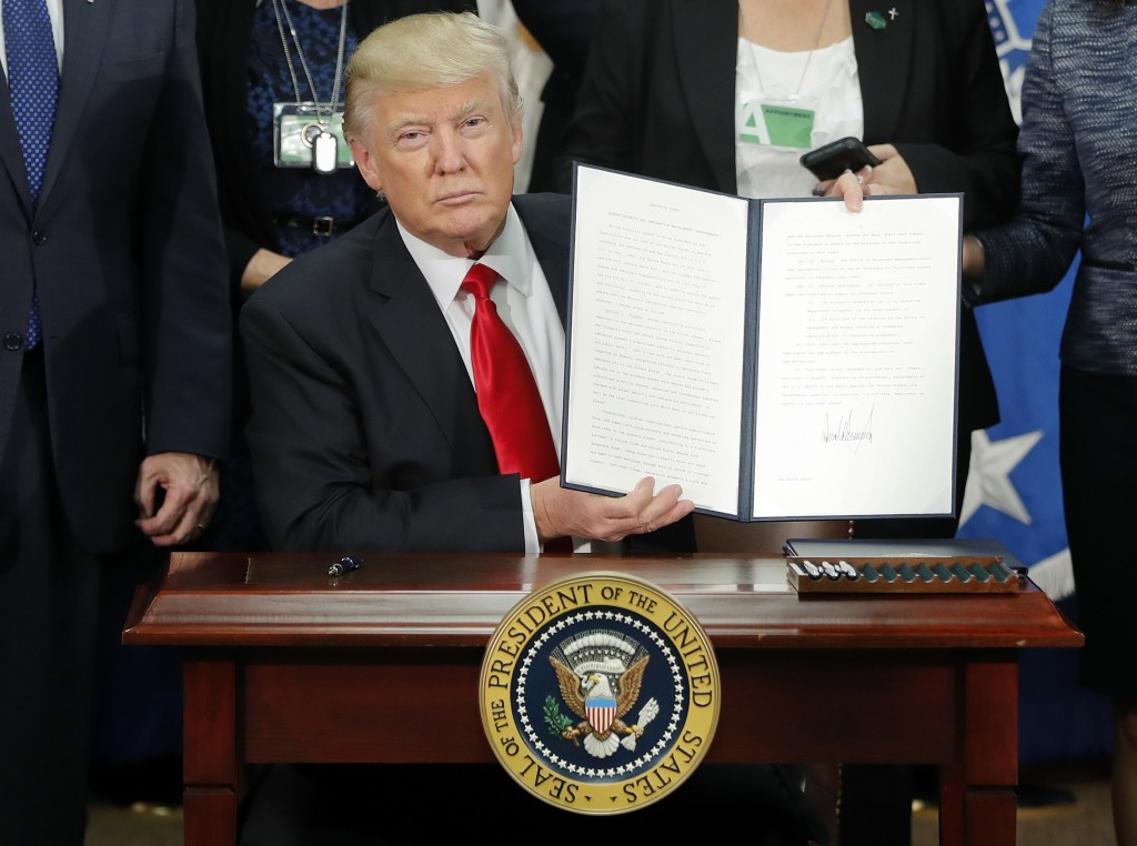 FILE - President Donald Trump holds up an executive order for border security and immigration enforcement improvements after signing the order during