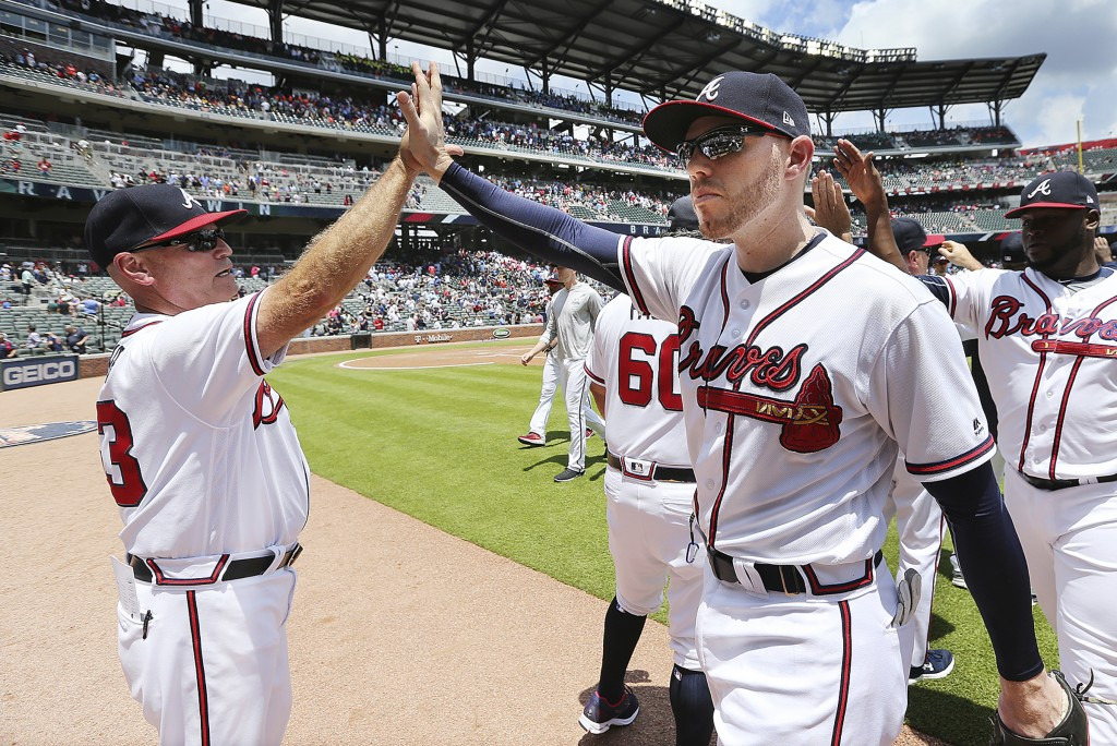 Atlanta Braves' Freedie Freeman, right foreground, gets a high five from manager Brian Snitker after the Braves defeated the New York Mets 2-0 in a ba...
