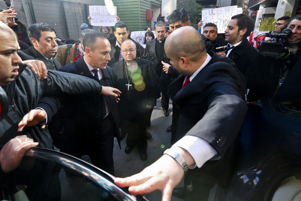 Archbishop Charles Scicluna, center left, and Monsignor Jordi Bertomeu, center right, are protected by security guards as university students demand t