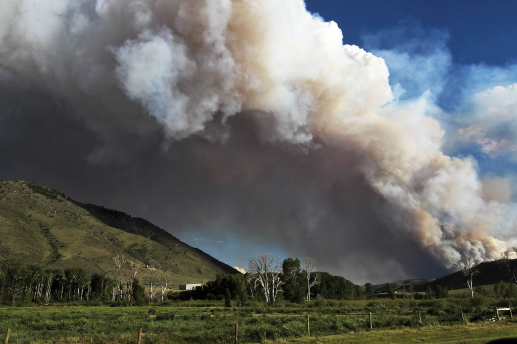 Smoke from a wildfire can be seen rising from the Medicine Bow National Forest near Woods Landing, Wyo., Wednesday, June 13, 2018. Several thousand pe