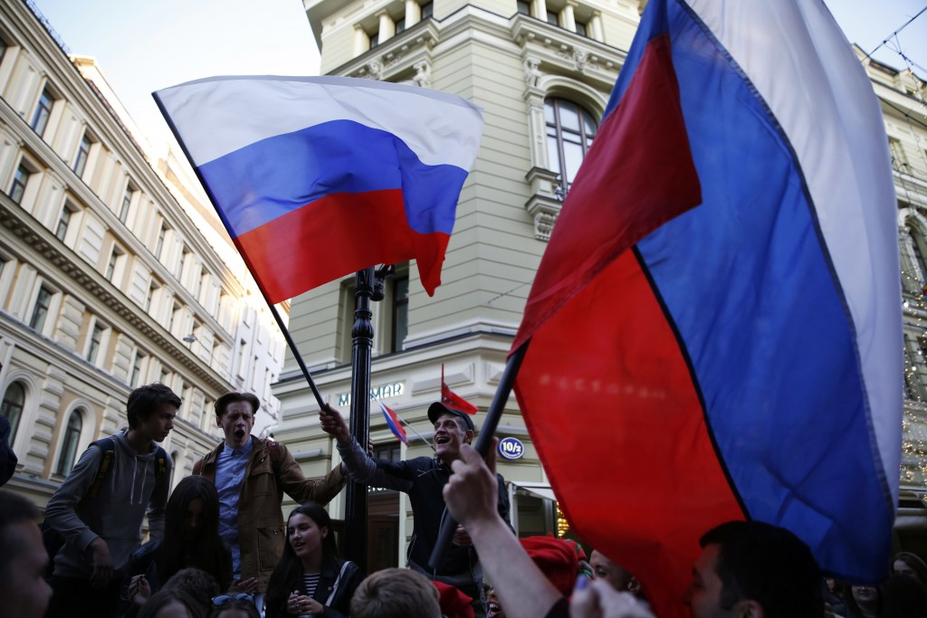 Russia fans wave national flags as fans from participating countries gathered on Nikolskaya Street to celebrate and to cheer on their teams, on the ev