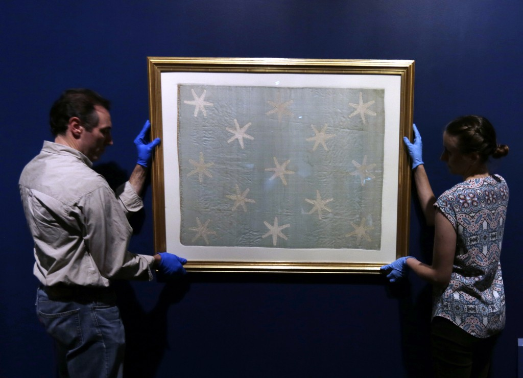 Collections manager Michelle Moskal, right, and curator Mark Turdo hang the Commander-in-Chief's Standard, Wednesday, June 13, 2018, at an exhibition