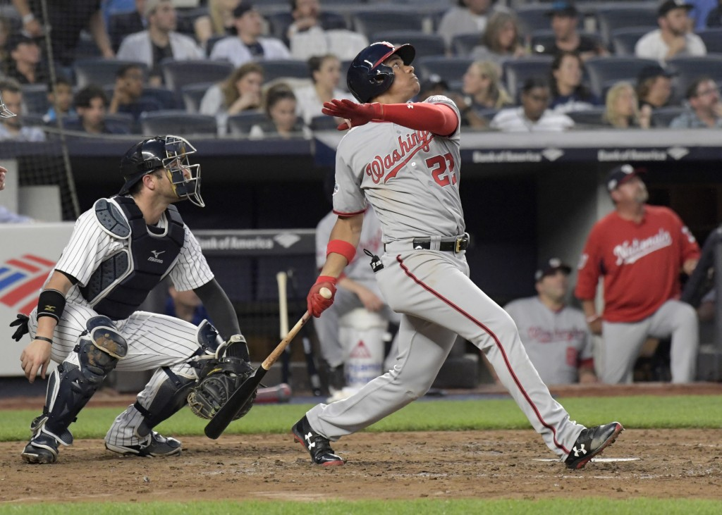 Washington Nationals' Juan Soto watches his three-run home run in front of New York Yankees catcher Austin Romine during the fourth inning of a baseba