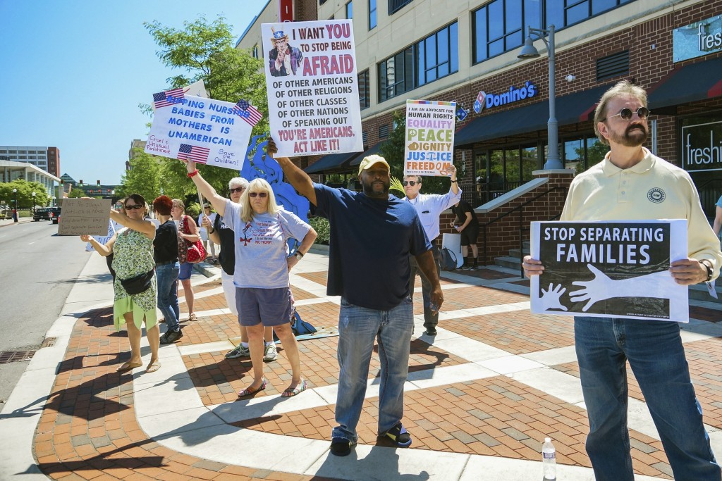People line up to protest U.S. Attorney General Jeff Sessions and immigration reform at Parkview Field in Fort Wayne, Ind., Thursday, June 14, 2018. (