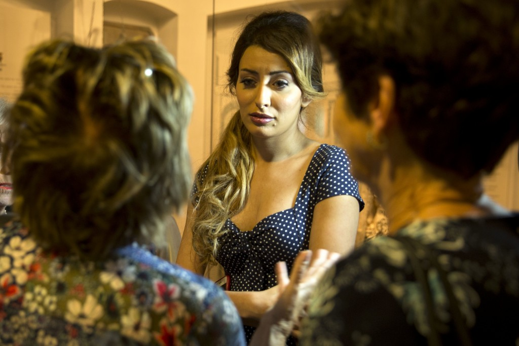 Sarah Idan, Iraq's 2017 Miss Universe beauty pageant contestant, center, speaks with other visitors during a visit to the Babylonian Jewry Heritage Ce