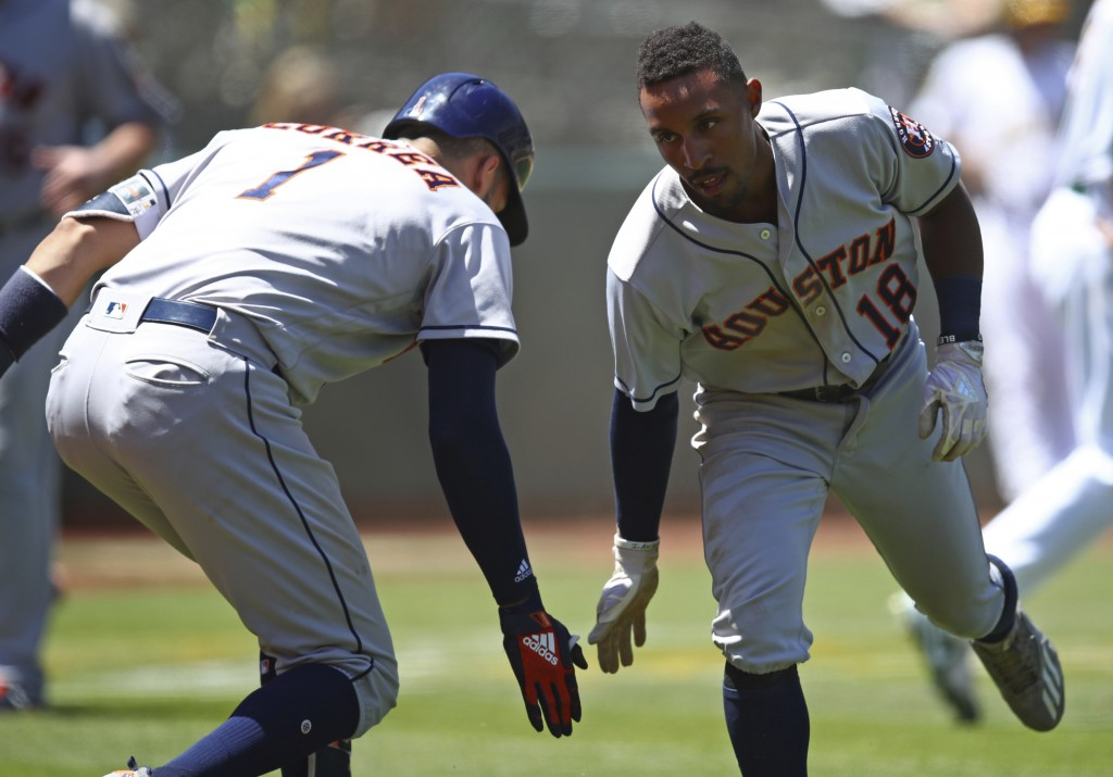 Houston Astros' Tony Kemp, right, celebrates with Carlos Correa (1) after scoring against the Oakland Athletics in the sixth inning of a baseball game