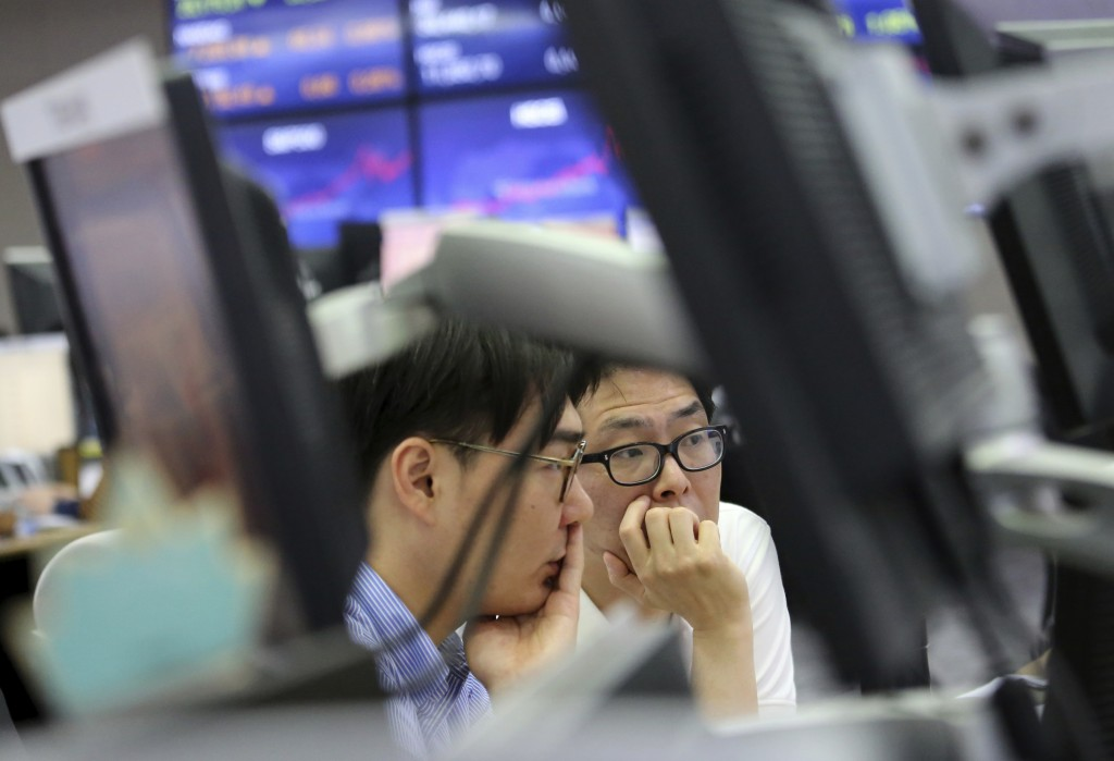 Currency traders watch monitors at the foreign exchange dealing room of the KEB Hana Bank headquarters in Seoul, South Korea, Friday, June 15, 2018. A...